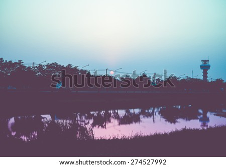 Vintage filtered : silhouette landscape of road beside tree and lagoon in sunset time. - stock photo