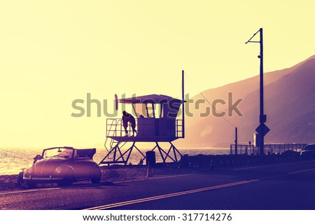 Vintage filtered sunset over beach with lifeguard tower, Pacific Coast Highway, USA. - stock photo