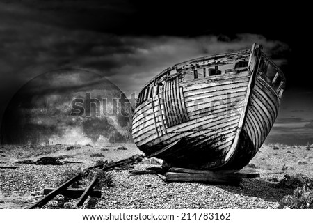 Vintage fishing boat. An old abandoned fishing boat stranded on a beech in black and white. Elements of this image furnished by NASA. - stock photo