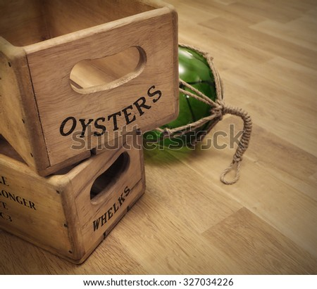 vintage fishmongers wooden boxes and green glass buoy on oak table with copy space - stock photo