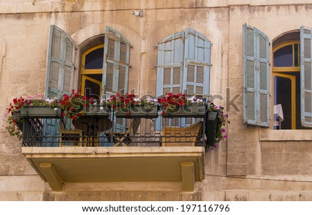 Vintage flowers decorated balcony in old house - stock photo