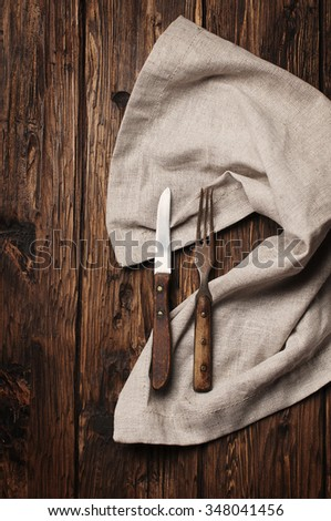 Vintage fork and knife on the wooden table, selective focus - stock photo