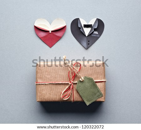 Vintage gift box with blank gift tag and symbolic male and female heart shapes on gray paper background. - stock photo