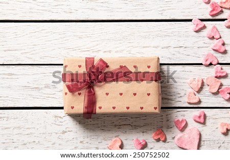 Vintage gift box with heap of small hearts on white wooden background. - stock photo