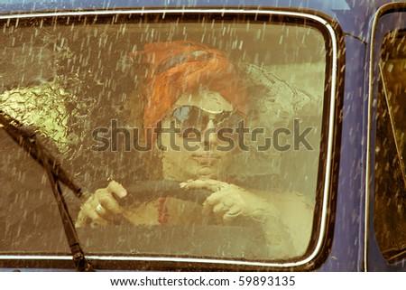 Vintage girl driving car under rain - stock photo