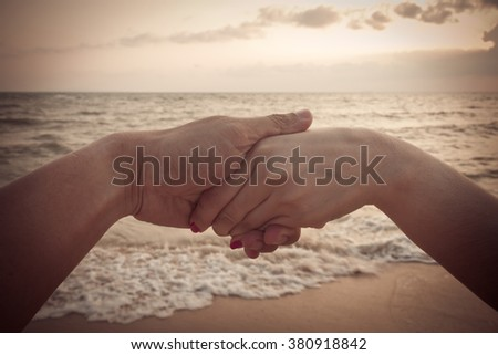 Vintage girls holding hands backdrop of the sea