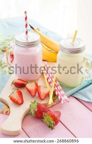 Vintage glass jars with milk and fresh strawberries and bananas - stock photo