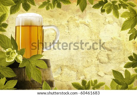 Vintage glass of beer on old barrel and hop plant on grunge background - stock photo