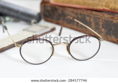 Vintage glasses in focus with old books and slide ruler out of focus