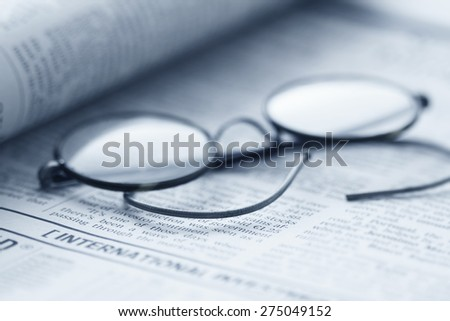 vintage glasses on newspaper - stock photo