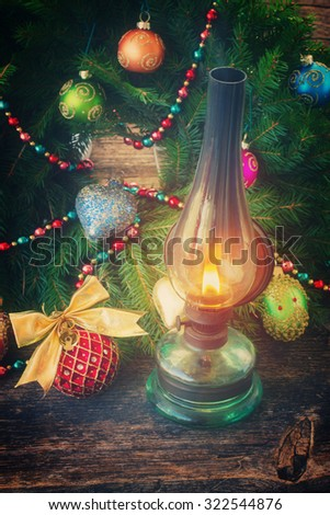 vintage glowing lantern with decorated christmas evergreen wreath, low key, retro toned - stock photo