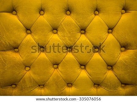 Vintage gold leather upholstery buttoned sofa (background) - stock photo