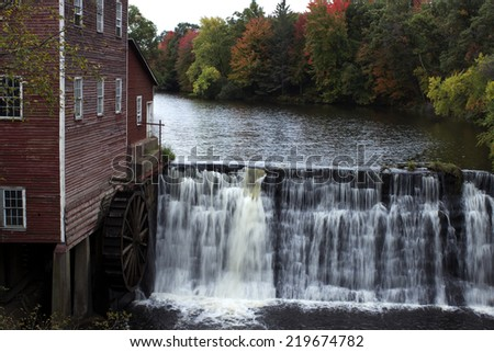 vintage grain mill with water wheel next to a small dam - stock photo