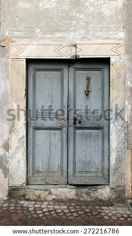 Vintage grey damaged wood medieval door in rural stone wall house, Italy - stock photo