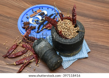 Vintage Grinding stone / stone blender and pestle for grinding spice Kerala, India. aromatic Indian spices, traditional curry masala preparation. Stone mortar coriander seeds and dry chilie pepper - stock photo