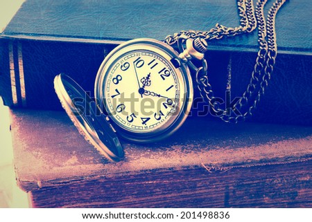 Vintage grunge  antique pocket watch, and old book    - stock photo