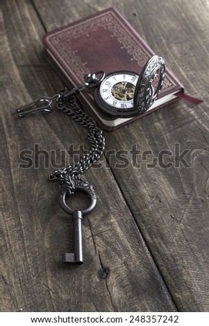 Vintage grunge still life with  pocket watch, old brass key and tattered book. - stock photo