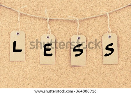 Vintage grunge tags with letters on rope string, word LESS over cork board texture background, filter applied, available copy space.  - stock photo