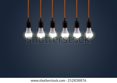 vintage hanging energy light bulbs on blue retro, background