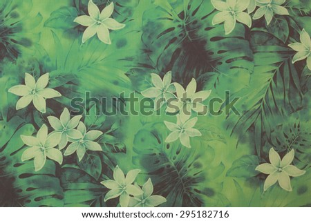 Vintage Hawaiian Aloha shirt cloth fragment with white Plumeria flowers and black and blue leaves on a faded green background. - stock photo
