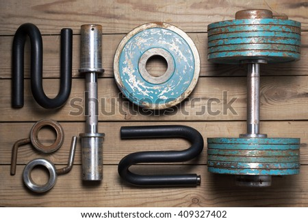 Vintage heavy dumbbell , dumbbell in disassembled form and stops for push-ups. Flat lay - stock photo