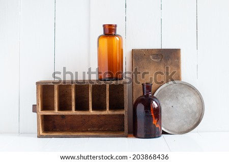 Vintage home decor: old wooden boxes and vintage brown glass bottles on white wooden board, retro home interior. - stock photo
