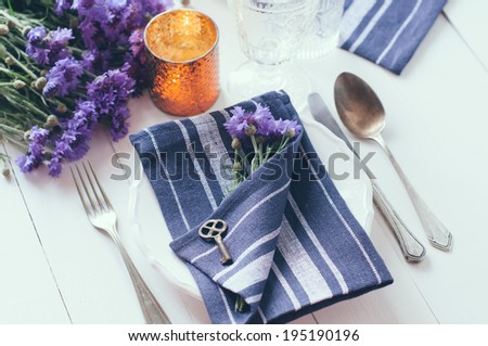 Vintage home table setting with blue napkins, antique cutlery, old key and purple cornflowers on white wooden table. - stock photo