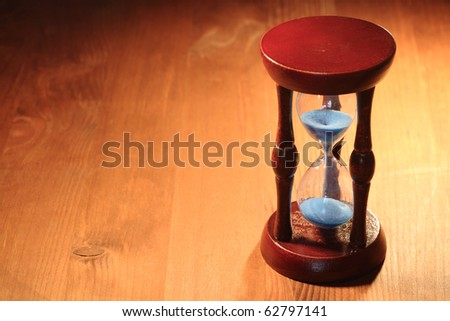 Vintage hourglass with blue sand standing on wooden background - stock photo