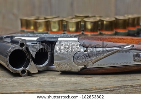 vintage hunting gun with cartridges on wooden background - stock photo