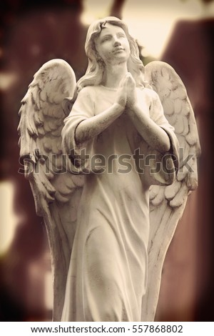 Vintage image of a sad angel on a cemetery against the background of leaves (details)