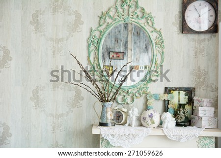 Vintage interior with mirror and a table with a vase and willows. Designer wall clock. Angels on the table - stock photo