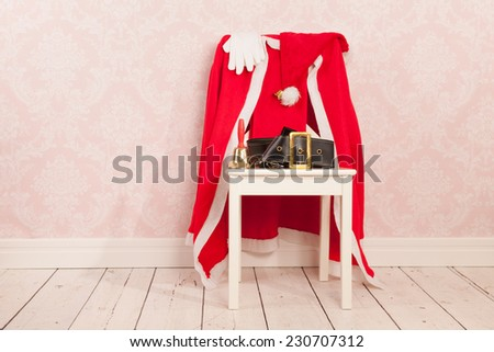 Vintage interior with old wall paper and chair with clothes from Santa Claus - stock photo