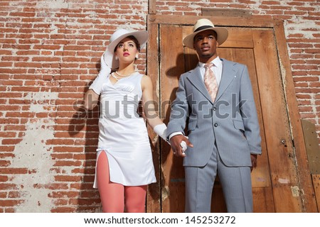 Vintage jazz fashion sexy wedding couple in old urban building. Mixed race. Wearing a hat. - stock photo