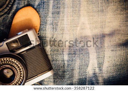Vintage jeans with belt and classic camera.