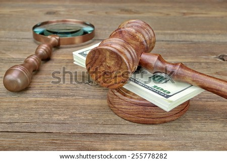 Vintage Judges Gavel, Sounboard, Magnifier and Money Wad on Grunge Wood Table - stock photo