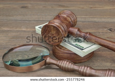 Vintage Judges Gavel, Soundboard, Magnifier and Money Wad on Grunge Wood Table - stock photo