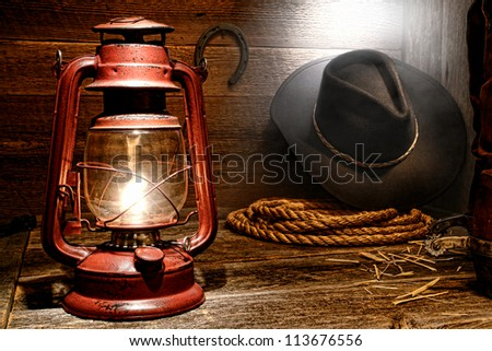 Vintage kerosene lantern lamp with American West rodeo cowboy gear with hat and ranching lasso rope near authentic leather roping boots in soft window light diffused in smoke in an old ranch wood barn - stock photo