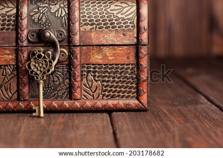 vintage key and old treasure chest on wooden table - stock photo