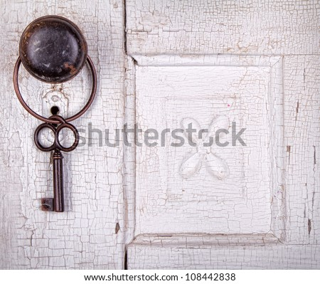 Vintage key hanging on a old cracked antique or vintage door