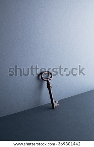 Vintage Key leaning against dark blue background with negative space