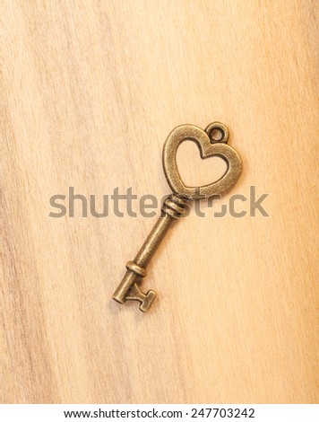 Vintage key with heart shape ring hole on wooden background - stock photo