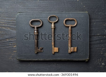 Vintage Keys over black leather book cover and wooden table, top view - stock photo