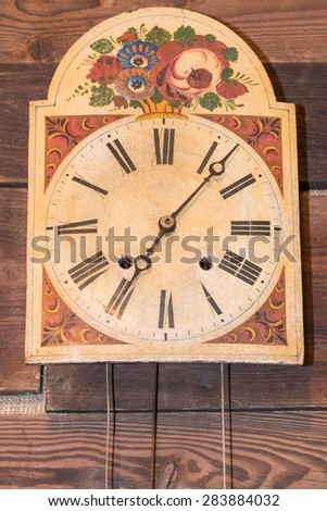 vintage kitchen clock with Roman numbers hanged on wooden background - stock photo