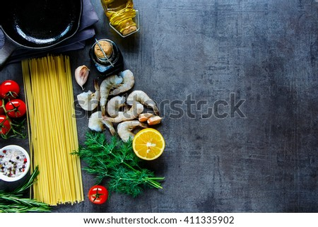 Vintage kitchen table and ingredients for pasta with seafood. Shrimps, spaghetti, dill, garlic, spices and cherry-tomatoes over grunge backdrop from above, place for text, border. - stock photo