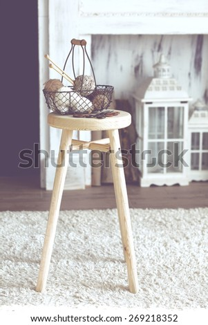 Vintage knitting needles, scissors and yarn inside old wire basket on wooden stool near fireplace, still life photo with soft focus - stock photo