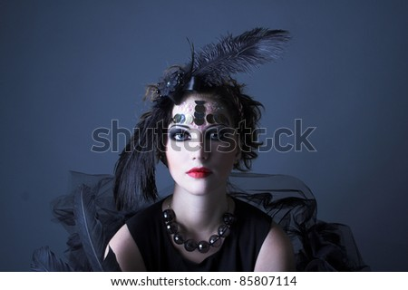 Vintage lady. Young woman in retro style and with feathers in her hair.