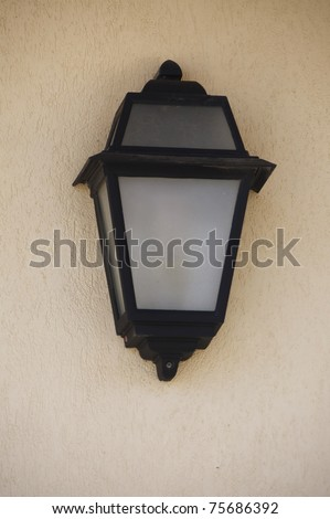 vintage lamp isolated on rough wall - stock photo