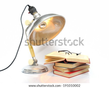 Vintage lamp with stack of books - stock photo
