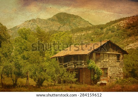 vintage landscape with an old house on a meadow near mountains  - stock photo