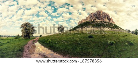 Vintage landscape with mountain, road and clouds reflection in puddle - stock photo